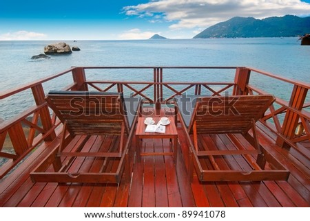 Beach beds on exotic terrace with romantic sea view - stock photo