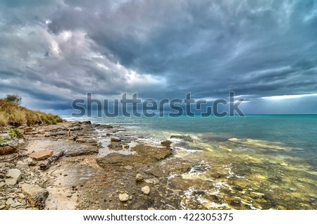 Beach before the storm hits. Dramatic hurricane clouds over the sea. - stock photo