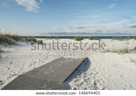 Beach boardwalk footpath meets the sand on beautiful Gulf Coast beach in the early morning. - stock photo