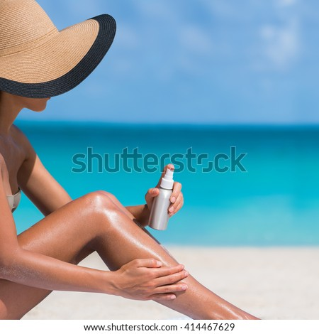 Beach body suntan skin care travel vacation. Bikini hat woman applying sunscreen lotion putting cream on tanned sexy legs sunbathing sun tanning sitting on sand with turquoise blue ocean background. - stock photo