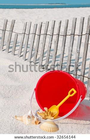 beach bucket and seashells by beach fence - stock photo