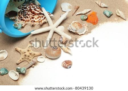 Beach bucket and shells on sand - stock photo