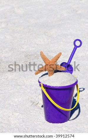 Beach Bucket with a Starfish and Shovel - stock photo