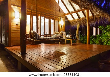 Beach bungalow at sunset - Maldives vacation background - stock photo