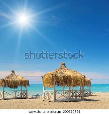 Beach, bungalows, blue sky and sun - stock photo