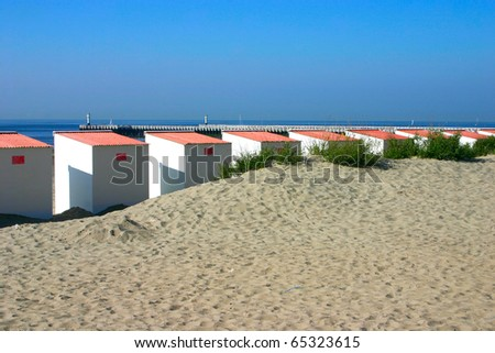 Beach cabins at the Belgian coast with pier in the background