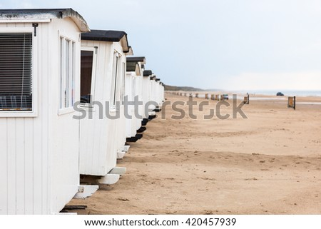 Beach cabins in a row on the sandy beach - stock photo