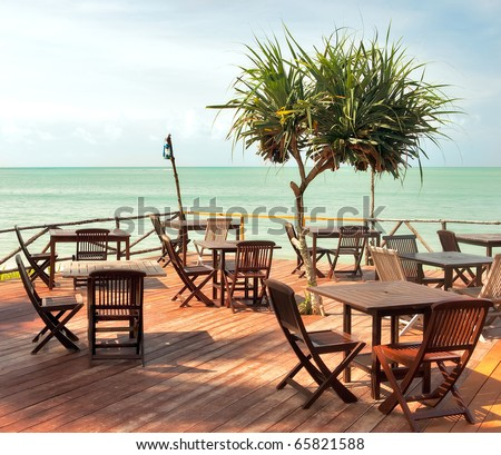 Beach cafe with wooden tables and chairs placed at the sea waterfront - stock photo