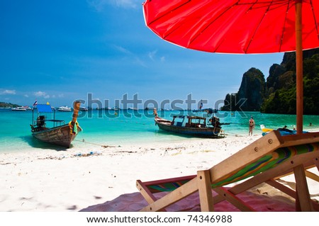 Beach chair and Long tailed boat at Phi-phi - stock photo
