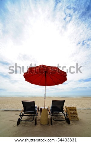 Beach chair and red umbrella on the beach , Huahin Thailand - stock photo