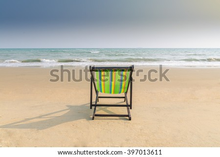 Beach chair and shadow on the white sand beach with sunset light sky (lonely concept) - stock photo