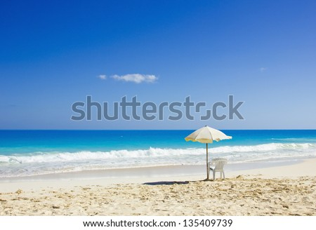 BEACH CHAIR AND UMBRELLA ON IDYLLIC TROPICAL SAND - stock photo