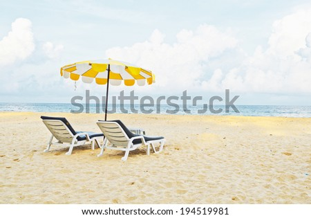 Beach chair and umbrella on sand beach - stock photo