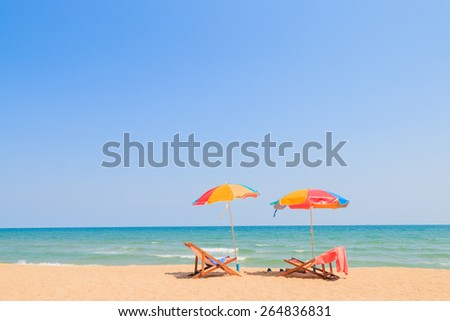 Beach chair and umbrella on sand beach - stock photo