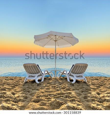 Beach chair and white umbrella on sand beach - stock photo