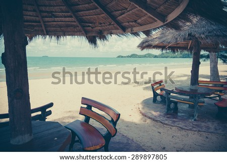 Beach chair and wooden umbrella on the beach ,Thailand - vintage effect style pictures - stock photo