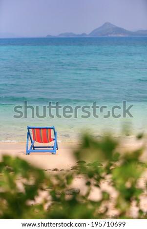 Beach chair on beach of turquoise ocean - stock photo