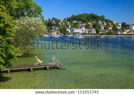 Beach chair on wooden jetty and mountain lake, Gmunden, Traunsee, Upper Austria