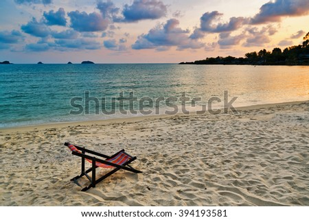 Beach chair set in the sand overlooking sea sunset. Thailand