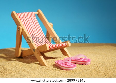 Beach chair standing on sea sand and pink flip flops with flowers and blue sky