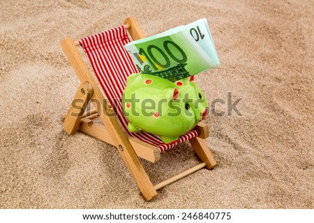 beach chair with euro currency on the sandy beach. symbolic photo for cost of travel, vacation, holidays - stock photo