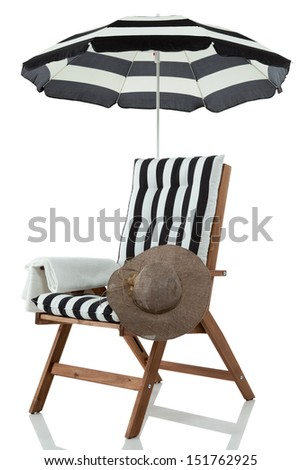 Beach chair with umbrella, hat and towel - stock photo
