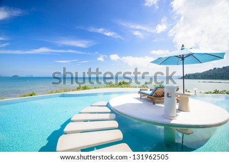 beach chair with umbrella on private pool, ocean view - stock photo