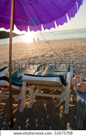 Beach chair with umbrella with view of sunset