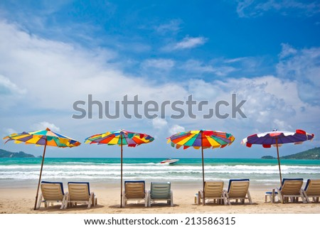 Beach chairs and colorful umbrella on the beach in sunny day at Phuket Thailand.