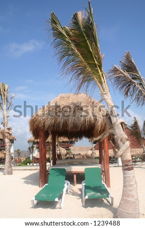 Beach chairs and palapa (bed) for the perfect ocean view - stock photo