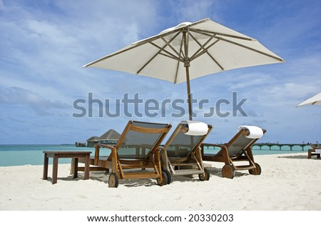 Beach chairs and parasol on white sand at the ocean - stock photo