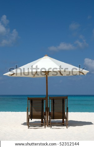 Beach chairs and umbrella on a sand beach in Maldives - stock photo