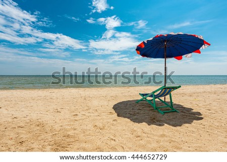 Beach chairs and umbrella on the white sand and sea under coconut tree with cloudy blue sky and sun  - stock photo