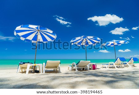 Beach chairs and umbrella on the white sand beach - stock photo