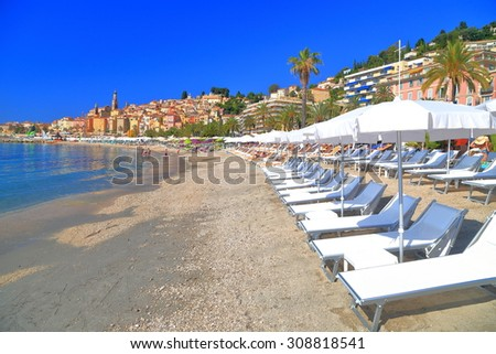 Beach chairs and umbrellas along sandy beach in Menton, French Riviera, France