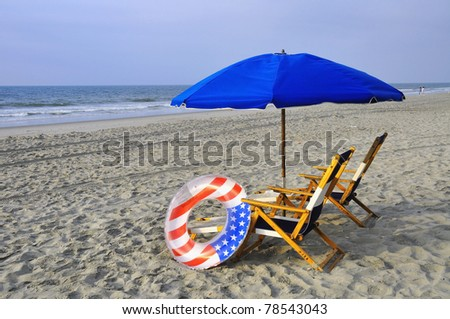 Beach Chairs and umbrellas by the sea shore - stock photo
