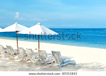 beach chairs and umbrellas on beautiful tropical sand beach - stock photo