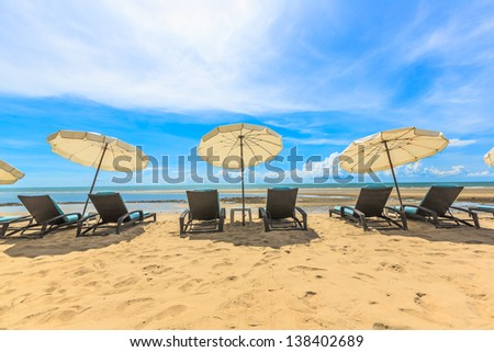 Beach chairs and with white umbrella and beautiful beach on a sunny day at hua hin beach - stock photo