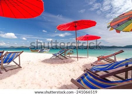 Beach chairs & colorful beach umbrellas on the beach at Koh Khai in Phang Nga province of Thailand
