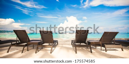 Beach chairs in exotic resort on perfect white sandy beach - stock photo