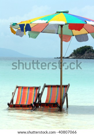 Beach chairs in water under colourful parasol