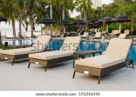 Beach chairs near swimming pool - stock photo