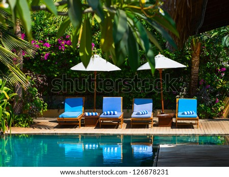 Beach chairs near swimming pool in tropical resort - stock photo