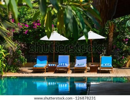 Beach chairs near swimming pool in tropical resort - stock photo