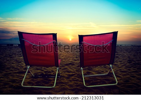 Beach chairs on looking at the sun.Selective focus on the chairs - stock photo