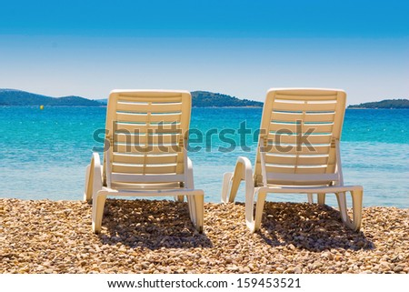 Beach chairs on pebble beach, beautiful blue sky and sea, island in background - stock photo