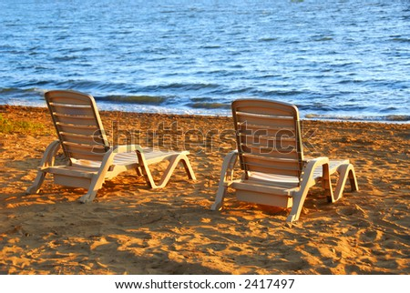 Beach chairs on sea shore in late afternoon