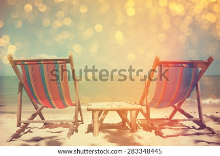 Beach chairs on sea shore with glowing bokeh and film stylized, double exposure effect - stock photo