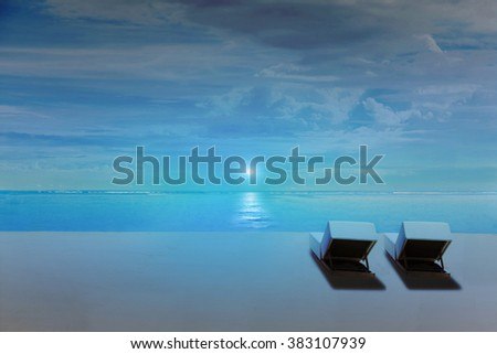 Beach chairs on the beach at night with moon rise, and dark blue environment - stock photo