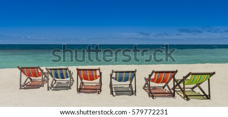Beach chairs on the beach with nice sea and blue sky background